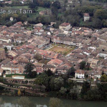 Lisle sur Tarn: La place aux couverts, ornée de la fontaine du Griffoul, est la plus grande du sud-ouest et témoigne encore de l'importante prospérité économique de cette cité.